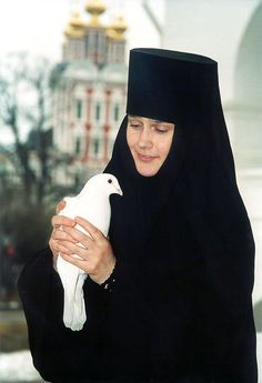 Nun with a pigeon in Moscow, Russia
