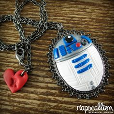 """We compacted R2D2 until he fit perfectly into this oval gunmetal cameo setting. Is it just me, or does he suddenly seem more dignified?  - Hand sculpted from polymer clay - Gunmetal cameo setting - Glazed for a nice shine - Rapscallion signature charm - Pendant measures approximately 2""""h x ..."""