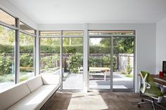 Located beside an outdoor dining area is a home office that's surrounded by large windows and sliding glass doors, filling the room with lots of natural light to work in.