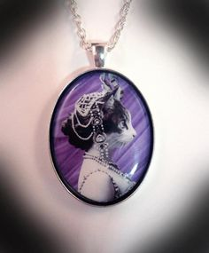 """Catahari - Completely unique artwork by The Clockwork Jewel, introducing the beautiful 'Catahari', an agent of some renown throughout the world. In a resin cover in a silver plated bezel. Chain length of your choice 16"""" - 18"""" - 20"""" - 22""""   Size - 4cm x 3cm.  £22.99 Now SOLD."""
