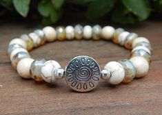 White and Cream Boho Bracelet made with 8mm Picasso Czech and Creamy Howlite Rondeles and 8mm Natural White Wood with a pretty Sun focal bead. Howlite Properties: This calming stone is said to teach p