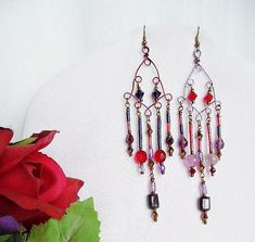 #elegancebydorianne #bohojewelry #shoulderdusters #gypsyjewelry #chandelierearrings #etsyjewelryshop #etsyjewelry #etsysellers #etsyshop #valentinesgiftforher       Delightfully Unusual Red and Purple Shoulder Duster Earrings that are opposite each other in beads and colors! Red and purple handcrafted