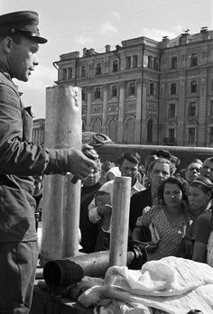 Soviet officer teaching civilians how to disarm an unexploded German incendiary bomb. Sverdlov Square in Moscow, Russia, 1 September 1941.