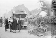 A group of women stand beside the wreckage of their homes following a V1 attack on the Highland Road and Lunham Road area of Upper Norwood, holding bedding and blankets as they chat to a Civil Defence worker.