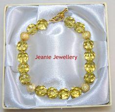 Esta pulseira amarela e dourada foi feita com pedras de vidro, esferas de metal e feixo douradoa. Esta pulseira foi feita na Inglaterra por mim.