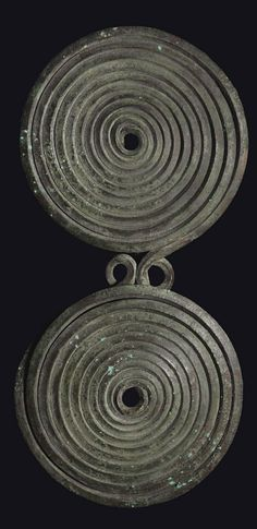 AN ITALIC BRONZE SPECTACLE FIBULA   CIRCA 8TH CENTURY B.C.   Formed from a single wire, square in section, coiled into two opposing spirals with a double loop in between, the pin and catch-plate preserved at the back  6 3/16 in. (15.7 cm.) wide