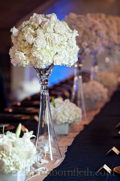 Mix of high and low centerpieces with white peonies, roses, hydrangea and stock