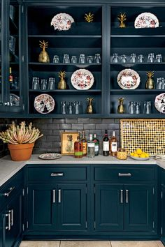 """Pantry - 2015 Charlottesville Idea House Tour - Southernliving. """"Navy cabinets and a ceramic graphite backsplash dress up the pantry, but the area is still functional,"""" says Rosney Co. Limestone counters, antique plates, and brass pineapples brighten up the space."""