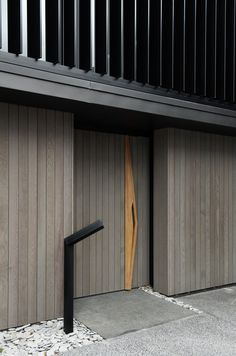 The vertical grey wood panels of this wood front door are interrupted by a sculptural door handle that runs the length of the door. Daniel Marshall Architects designed this modern house in New Zealand. Photography by Emily Andrews & Ernie Shackles. Modern Entrance, Modern Entryway, Entrance Doors, Doorway, Modern Wood Doors, Wood Front Doors, Wooden Doors, Architecture Details, Interior Architecture