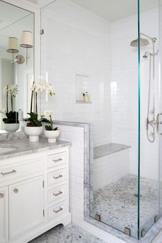 A glass-enclosed shower is fitted with a bench is this traditional master bathroom space. The potted flowers on the vanity are also seen in the kids' bathroom, adding continuity between the spaces.