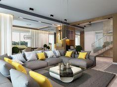 salon moderne avec un canapé gris décoré de coussins en jaune, gris et bleu clair, suspensions noir mat et table basse blanche