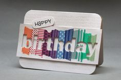 handmade birthday card ... BIRTHDAY die cut from panel with strips of colorful washi tape ... negative space shows the white card background ...