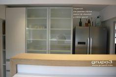 grupo3.cocina Maru. vista a través de la barra. Amplias despensas con puertas vitrina con marco de aluminio y vidrio opacid.