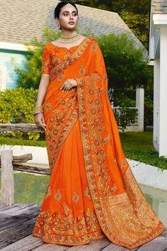 Orange satin silk saree with orange art silk blouse. Saree embellished with resham work, stone and zari work. Saree with Sweetheart Neckline, Half Sleeve. It comes with unstitch blouse, it can be stitched to 32 to 58 sizes. #weddingsaree #weddingwearsaree #festivalwear #partywearsaree