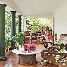 open air porch with dark green colonial columns and oversize wooden lounge chairs set around a coffee table with a tree stump base