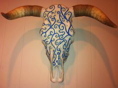 Royal blue, turquoise, yellow, and gold hand painted cow skull.