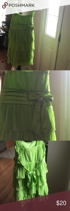 Girl's Green Sparkly Dress This dress is really cute and really comfy! It has sparkles/glitter all over and cute ruffles down the dress! It has a bow to tie in the back and is a stretchy material! It is cute for a party or just for fun! It's in great condition and does not have any tears, holes or stains on it! Dresses