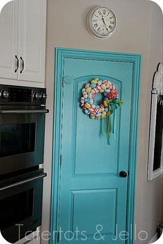 plastic eggs wrapped with washi tape; hot glue to a wreath form; add a pinwheel and big bow. I think I love the blue door more than the wreath, though!