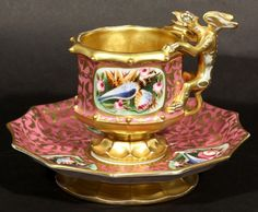 ANTIQUE RUSSIAN KORNILOV PORCELAIN CUP AND SAUCER WITH GRIFFIN HANDLE, KOMILOV BROTHERS FACTORY, CICRA MID 19TH CENTURY. CUP AND SAUCER BOTH OF DECAGONAL FORM ON FLRED , EXTERIOR OC CUP AND CAVETTO OF SAUCER INTRICATELY DECORATED WITH GILT SCROLLING FOLIAGE ON PINK GROUND, SURROUNDING CARTOUCHES HAND PAINTED WITH IMAGES OFSEASHELLS AND FLOWERS, INTERIOR OF CUP IS FULLY GILDED