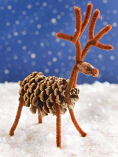 Cut a brown pipe cleaner in half, then wrap one piece around each end of a pinecone, bending the pipe cleaners into legs. For the neck and head, fold a pipe cleaner in half, then in half again. Push the two middle folds into an oblong wooden bead until the pipe cleaner just pokes through. You'll have a folded loop and two ends sticking out of the other end of the bead: Bend the two ends up for the antlers. Bend the loop down and slip it onto the end of the pinecone for the neck. I...