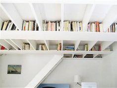 Majitel knih využil nízkého stropu, vzal prkna a překližku, natřel je na bílo a
