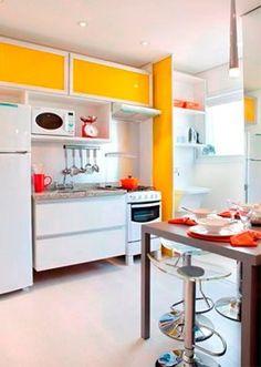 Os armários superiores e a divisória para área de serviço em amarelo deram vida a esta cozinha