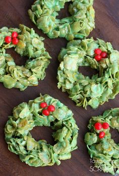 5 cornflake wreath desserts laying on a wooden board and topped with three red hot candies to look like a Christmas wreath.