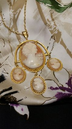 Item Description: Statement Pendant composed of an antique hand carved shell cameo accentuated by three dangling mini shell cameos set in 10K solid yellow gold Condition: Central Shell Cameo from the 1920- 30's Overall Dimensions: 4 inches x 2.5 inches