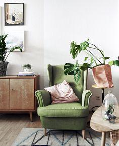 Poltrona verde accanto a una pianta in vaso e a un tavolino.