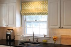 Hanging outside-mount Roman shade to align with top of curtain panel gives the room a better sense of proportion. Keep it closed enough just to cover the top.