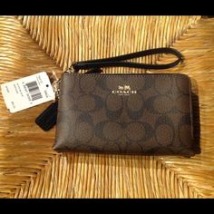 """Coach Signature Double Zip Wristlet Signature Coach Double Zip Wristlet with a detachable strap. Zippers go across the top and down one side.  Interior on one side has 2 id slots. 6.25"""" x 3.75"""" x 1.25"""".  Comes with a Coach care card, gift box, and gift bag. No Trades Coach Bags Clutches & Wristlets"""