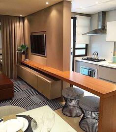 Sala de estar dividindo espaço com a cozinha por um imenso painel e uma bancada em mdf, indicando a linearidade entre os ambientes.