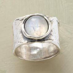 "LUNAR REFLECTIONS RING -- Our lunar reflections moonstone ring, a sterling interpretation of a full moon shining upon a rippling sea, is hand cast and set with an opalescent moonstone. Sundance exclusive in whole sizes 5 to 9. Approx. 1/2""W."