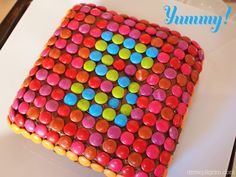 """Smarties cake. We used M and Ms and it looks great! The colors on some of the M and Ms did start to fade a bit (after being on for a few hours) as the color must have getting absorbed into the icing but they did not actually """"bleed"""" onto the icing. The contrast in color showed off the number 4 we made really well!"""
