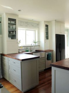 I've been thinking about butcher block counter tops and subway tile... this gives me an idea of what our kitchen would look like... our cabinets are two-toned like this.