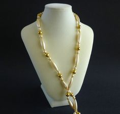 Vintage pearl necklace by Napier. This is a beautiful one strand necklace with elongated faceted lucite pearl beads followed by some round glass faux pearls and gold tone round beads. The Napier mark is found on the clasp.