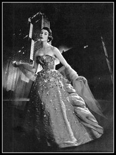 Myrtle Crawford is wearing gala ball gown of dark gray organdy embroidered with frosted multi-colored sequins, the back is made of organza ruffled waves from small to wider, worn with light gray tulle stole by Jacques Fath, photo by Pottier, 1953