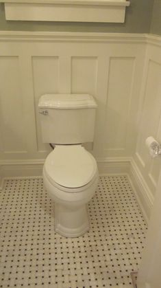 A bit of moulding and a black and white basket-weave tiled floor add vintage charm to a new bathroom!