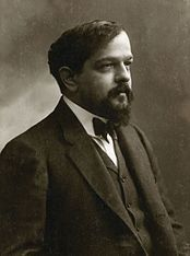A man with a beard and moustache facing right wearing a black jacket and bow tie.