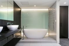 The same bathroom from another angle exposes the modern shape of the bathroom and the frosted glass window beside it. Lights on both the top and the bottom of the glass give it a dazzling glimmer. Bathroom Spa, Modern Bathroom, Bathroom Ideas, Washroom, Bathroom Renovations, Minimalist Bathroom, Modern Minimalist, Victoria And Albert Baths, Frosted Glass Window