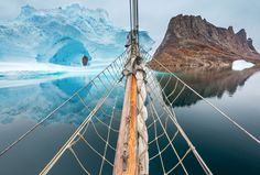DECEMBER 23, 2016 SOMETHING'S IN THE WAY A sailboat heads toward an iceberg and its rocky look-alike in eastern Greenland's Scoresby Sund, a Greenland Sea inlet that branches into an intricate network of fjords.  PHOTOGRAPH BY MIKE LONG, NATIONAL GEOGRAPHIC YOUR SHOT