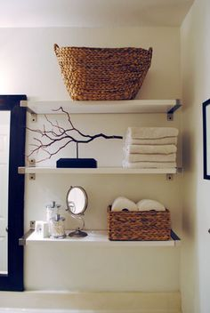 Floating shelves in the bathroom with woven baskets and stacked towels, sculptural wood art.