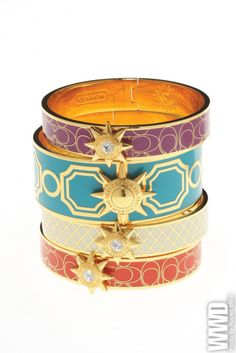 womensweardaily:    Tony Duquette Lives On at Coach  Enamel and gold-plated brass bangles with Swarovski crystal starbursts.