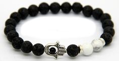 This bracelet features stunning Matte black lava beads, & White marble styled accent beads. The piece is finished with A Hamsa hand symbolizing peace within. This piece is as classy as they come. FREE