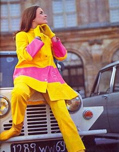 Model wearing a pink and yellow raincoat, 1960s.