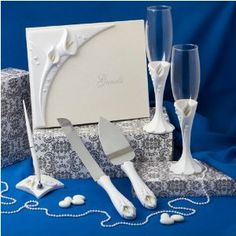 Calla Lilly Wedding Accessory Set (Guestbook, Champagne Flutes & More), 1 by Fashioncraft. $61.79. Package Contains 1 Set. Calla Lily Themed Wedding Sets White Poly Resin Calla Lily Design AppliquésIncludes Two Toasting Flutes, Cake Knife and Server Set, Guest Book and Pen SetPresented in Clear Acrylic Topped Display Gift BoxA beautiful symbol of strength and love, the calla lily themed wedding set is perfect for your special day. The set includes all the wedding accessori...