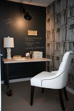 This is stripped-down cozy. The black, white and shades of gray keep the palette clean and allow for eclectic touches, like the library wallpaper, chalkbaord wall and funky table lamp.
