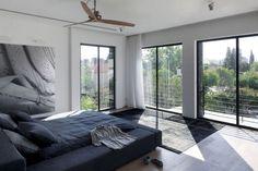 schlafzimmer fensterfront graues polsterbett schwarz weißes großes poster