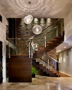 Stunning wood Stairway with stone background wall illuminated from above