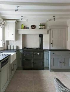 Kitchen with lower cabinets painted in Pigeon Estate Eggshell & upper and beams in Shaded White both Farrow & Ball